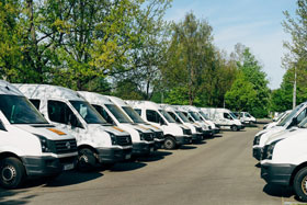 Fleet of White Vans in Parking Lot