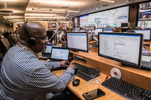 Man with Headset Works on Multiple Monitors in Large Control Center